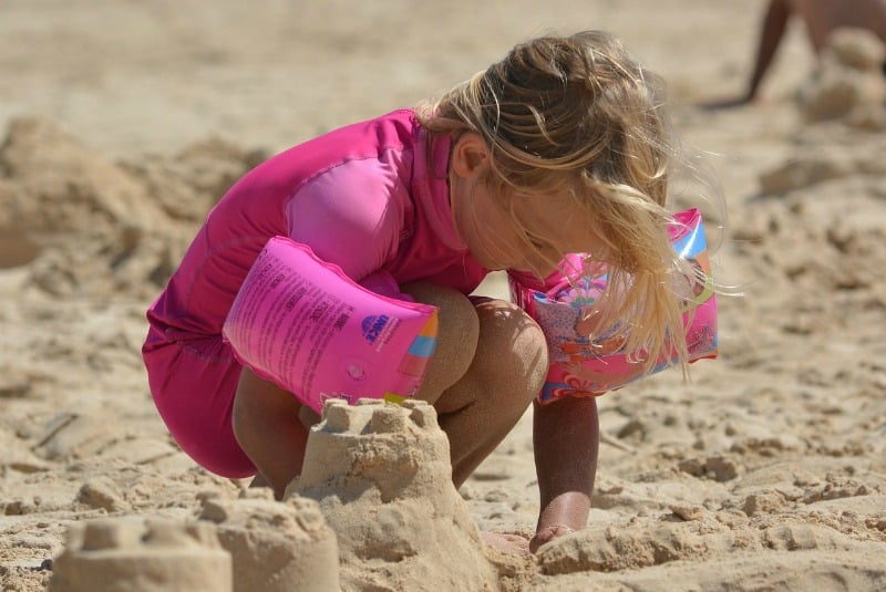 little girl wearing pink playing in the sand